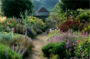 Parham. Sussex. Cool colour borders in summer. Path with view through to dovecote